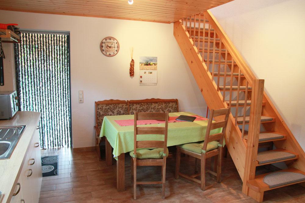 Ferienhaus mit Esstisch und Treppe zum Schlafzimmer